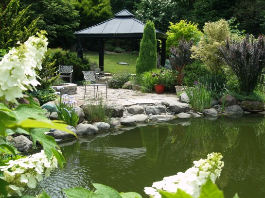 Looking across the koi pond to the stone patio and pavilion